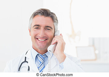 Doctor using landline phone in clinic - Portrait of happy...