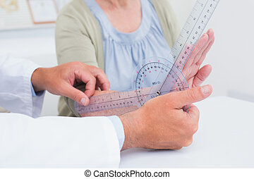 Physiotherapist examining patients wrist with goniometer