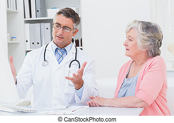 Doctor explaning reports to patient on computer - Male...