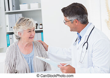 Doctor consoling senior woman in clinic - Male doctor...