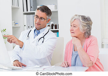Doctor showing reports to senior patient on computer - Male...