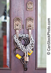 Part of wooden door with chain and lock.