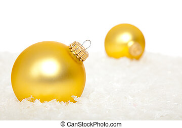 Gold Christmas ornaments in snow - Gold christmas ornaments...