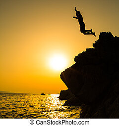 Boy jumping to the sea. Silhouette shot against the sunset...