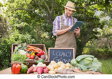 Farmer selling organic veg at market on a sunny day