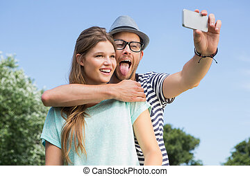 Cute couple in the park taking selfie on a sunny day