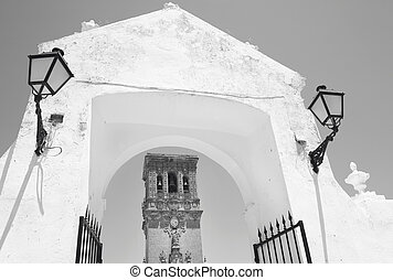 Andalusian traditional facade and arch with lamps Spain...