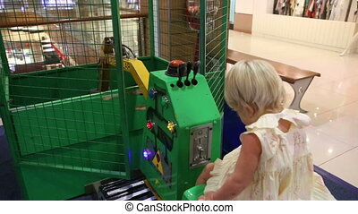blonde girl sits in toy excavator to control it - little...