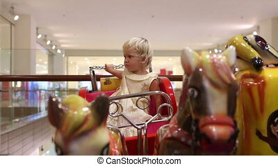 little blonde sitting in toy coach with horses