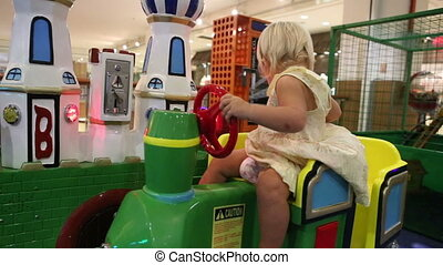 little blonde child is happy sitting in toy railway - little...