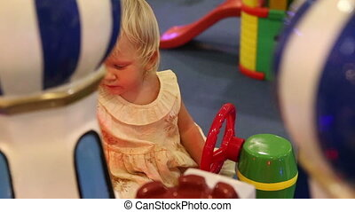 child sitting behind the wheel of toy car - little blonde...