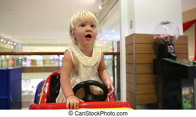 blonde child asks mother to get off toy car - little blonde...