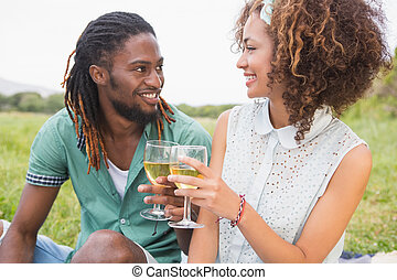 Young couple on a picnic drinking