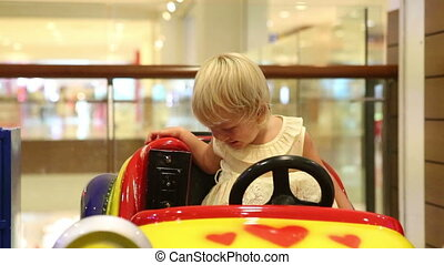 little blonde child happy sitting in toy car