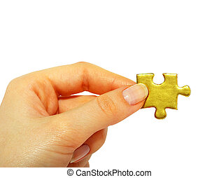 gold puzzle - woman fingers holdings gold puzzle on white