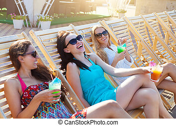 Girls with beverages on summer party near the pool - Happy...