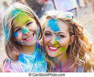 Happy mother with little daughter on holi festival -...