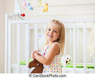 Little cute girl in nursery room with toys and wooden horse