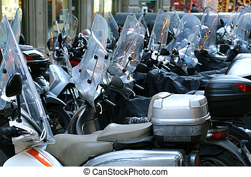scooters and mopeds with winter windshield parked in the...