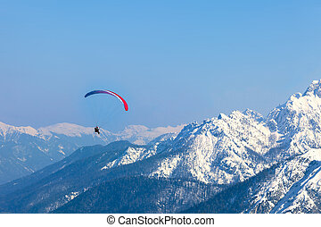 Paragliding - A man having fun with a paraglider over the...