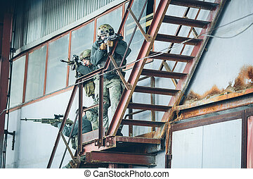 three soldiers climb the stairs at the factory - three...