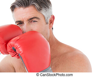 Fit man punching with boxing gloves on white background