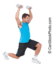 Fit man lifting dumbbells while lunging on white background