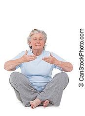 Senior woman doing yoga exercise