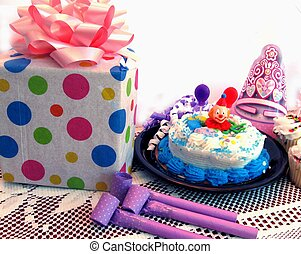 Birthday cake with present, party hats and noise blowers