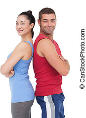 Fit man and woman smiling at camera together on white...