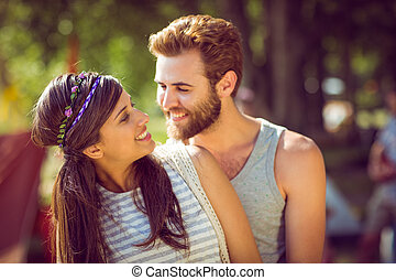 Hipster couple smiling at each other at a music festival