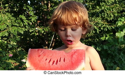 Ripe Watermelon and Child - Little golden-haired boy eating...