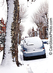 Snow covered cars in a Victorian terraced street in London...