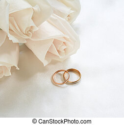 Wedding rings and roses as background