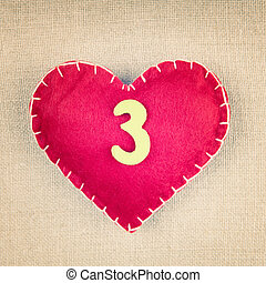 Red heart with wooden number 3 on vintage fabric background