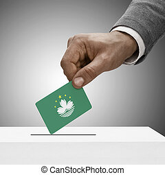 Black male holding flag. Voting concept - Macau