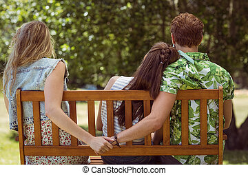 Young man holding hand of wrong girl on a summers day