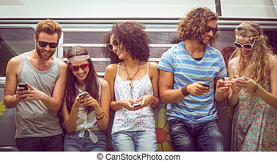 Hipster friends using their phones on a summers day