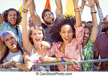 Excited young people singing along at a music festival