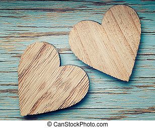 Two wooden hearts placed nicely on a turquoise vintage wood...