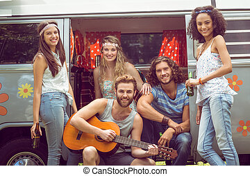 Hipster friends in camper van at festival on a summers day