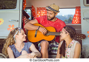 Hipster friends by their camper van on a summers day