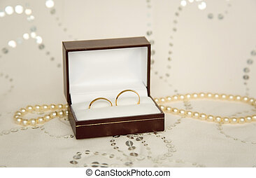Two golden wedding rings with pearl necklace and bridal veil