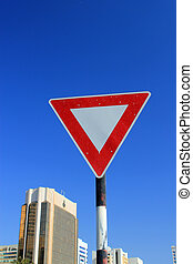 Yield triangle traffic sign against a blue sky with modern...