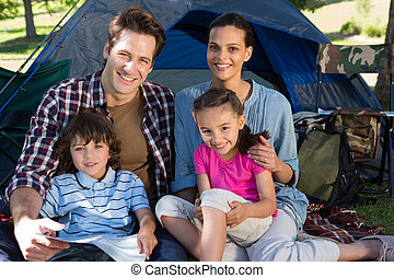 Happy family on a camping trip in their tent