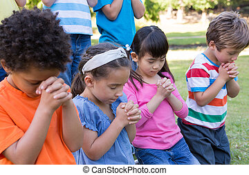 Children praying in the park - Children saying their prayers...