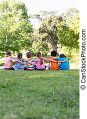 School children sitting on grass on a sunny day