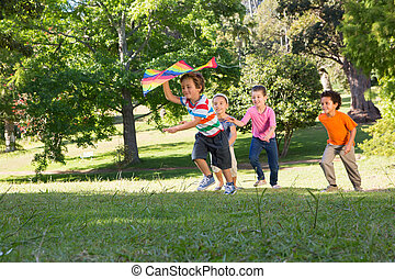 Children playing with kite in park on a sunny day