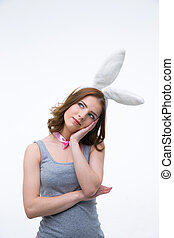 Pensive woman in rabbit ears looking up at copyspace