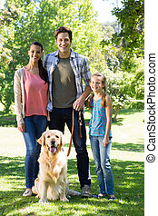 Happy family walking their dog in the park on a sunny day